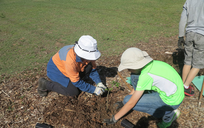 An Albany Hills State School student gets a few pointers from Dawn Road Reserve Bushcare group patron, Janet Mangan.